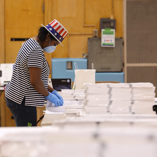 A woman with a patriotic hat on sorts through mail ballots